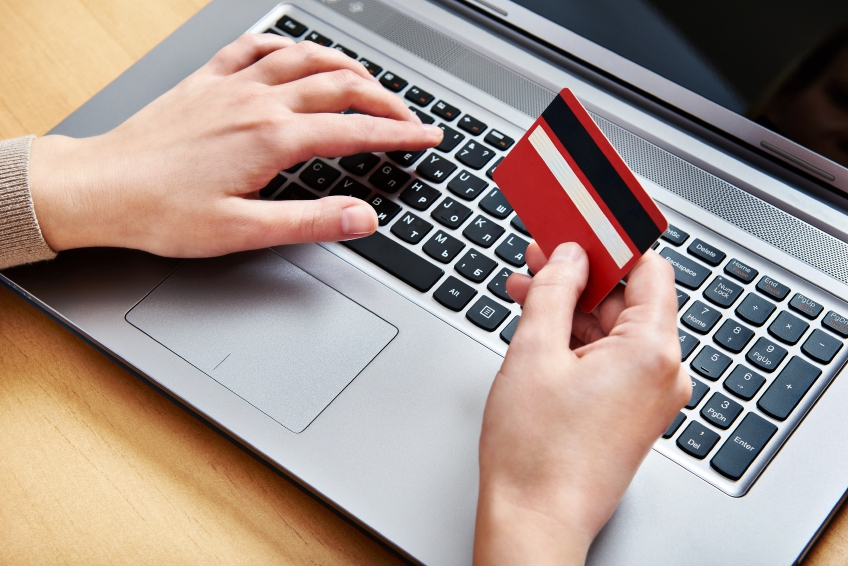 Image of a hang holding a credit card, whilst another hand hovers over a laptop keyboard ready to type.